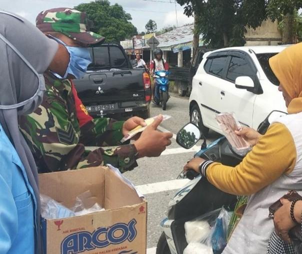 Mahasiswa UNRI, Babinsa Bangkinang,Kades Ridanpermai Bagikan Masker ke Pengendara untuk Cegah Corona